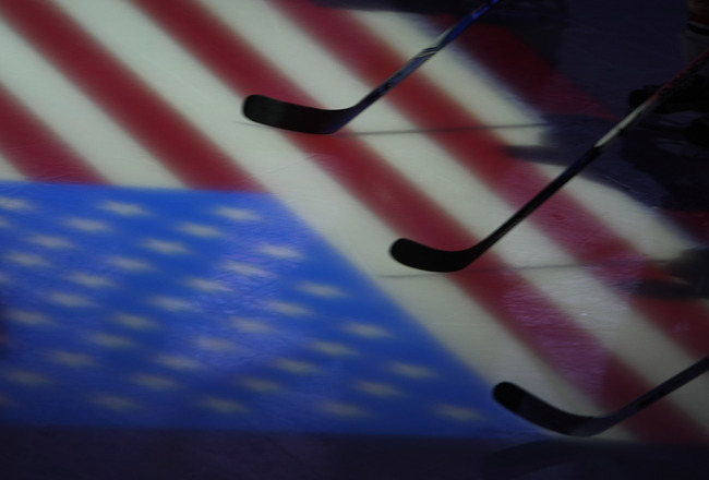ANAHEIM, CA - OCTOBER 15:  Players rest their sticks on a projection of the American flag during the national anthem before the game between the Anaheim Ducks the Edmonton Oilers on October 15, 2008 at the Honda Center in Anaheim, California. The Oilers w