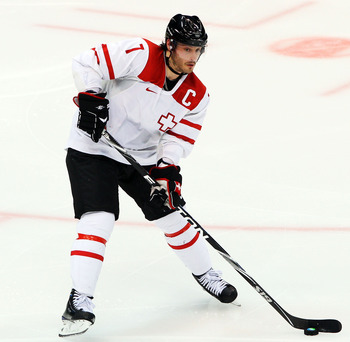 VANCOUVER, BC - FEBRUARY 24:  Mark Streit #7 of Switzerland handles the puck during the ice hockey men's quarter final game between USA and Switzerland on day 13 of the Vancouver 2010 Winter Olympics at Canada Hockey Place on February 24, 2010 in Vancouve