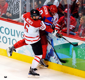VANCOUVER, BC - FEBRUARY 24:  Shea Weber #6 of Canada checks Alexander Ovechkin #8 of Russia into the boards during the ice hockey men's quarter final game between Russia and Canada on day 13 of the Vancouver 2010 Winter Olympics at Canada Hockey Place on