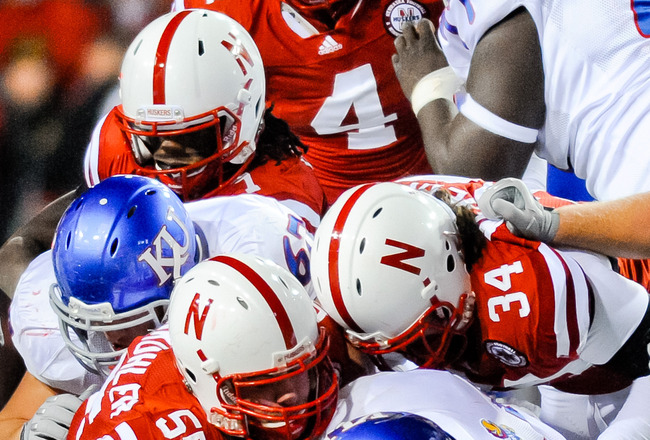 LINCOLN, NE - NOVEMBER 13: The Nebraska Cornhusker defense swarms James Sims #29 of the Kansas Jayhawks during their game at Memorial Stadium on November 13, 2010 in Lincoln, Nebraska. Nebraska Defeated Kansas 20-3. (Photo by Eric Francis/Getty Images)