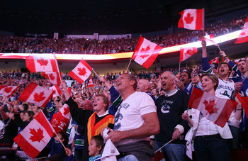VANCOUVER, BC - JUNE 15:  Vancouver Canucks fans wave the Canadian flag prior to Game Seven between the Vancouver Canucks and the Boston Bruins in the 2011 NHL Stanley Cup Final at Rogers Arena on June 15, 2011 in Vancouver, British Columbia, Canada.  (Ph