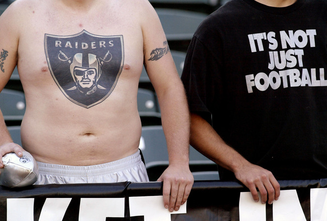 OAKLAND, CA  - OCTOBER 20:  Oakland Raiders fans, including one with a full chest tatoo, watch warmups before he game with the Kansas City Chiefs on October 20, 2003 at Network Associates Coliseum in Oakland, California.  (Photo by Stephen Dunn/Getty Imag