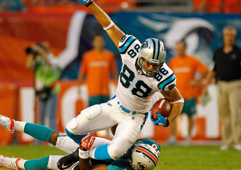 MIAMI GARDENS, FL - AUGUST 19:  Greg Olsen #88 of the Carolina Panthers is tackled by Karlos Dansby #58 of the Miami Dolphins during a preseason NFL game  at Sun Life Stadium on August 19, 2011 in Miami Gardens, Florida.  (Photo by Mike Ehrmann/Getty Imag