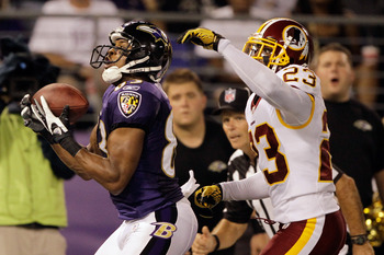 BALTIMORE, MD - AUGUST 25: Wide receiver Lee Evans #83 of the Baltimore Ravens catches a touchdown pass against defender DeAngelo Hall #23 of the Washington Redskins during the first half of a preason game at M&T Bank Stadium on August 25, 2011 in Baltimo