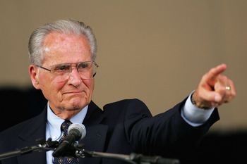 COOPERSTOWN, NY - JULY 31:  Jerry Coleman points to his wife in the crowd after receiving the Ford C. Frick Award, presented annually to a baseball broadcaster for major contributions to the game, during the Baseball Hall of Fame induction ceremony on Jul