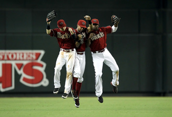 PHOENIX, AZ - AUGUST 28:  Outfielders (L-R) Collin Cowgill #4, Chris Young #24 and Justin Upton #10 of the Arizona Diamondbacks celebrate after defeating the San Diego Padres in the Major League Baseball game at Chase Field on August 28, 2011 in Phoenix,