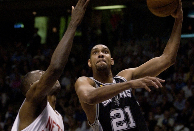 EAST RUTHERFORD, NJ - JUNE 13:  Tim Duncan # 21 of the San Antonio Spurs puts a shot up over Dikembe Mutombo #55 of the New Jersey Nets in Game five of the 2003 NBA Finals at Continental Airlines Arena on June 13, 2003 in East Rutherford, New Jersey.  The