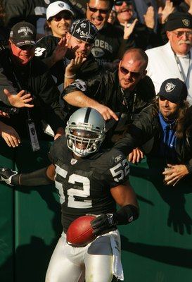 OAKLAND, CA - DECEMBER 3:  Kirk Morrison #52 of the Oakland Raiders celebrates with fans after scoring a touchdown against the Houston Texans during the second quarter of an NFL game on December 3, 2006 at McAfee Coliseum in Oakland, California.  (Photo b