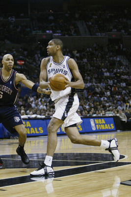 SAN ANTONIO, TX - JUNE 15:  Tim Duncan #21 of the San Antonio Spurs drives to the basket against Kenyon Martin #6 of the New Jersey Nets in game six of the 2003 NBA Finals on June 15, 2003 at the SBC Center in San Antonio, Texas.  The Spurs won 88-77 and