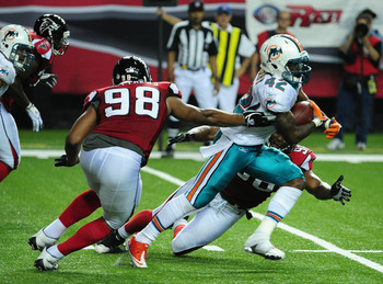 ATLANTA - AUGUST 12:  Nic Grigsby #42 of the Miami Dolphins carries the ball against Cliff Matthews #98 of the Atlanta Flacons during a preseason game at the Georgia Dome on August 12, 2011 in Atlanta, Georgia.  (Photo by Scott Cunningham/Getty Images)