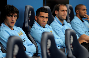 BOLTON, ENGLAND - AUGUST 21:  Carlos Tevez of Manchester City (2nd on L) watches from the bench during the Barclays Premier League match between Bolton Wanderers and Manchester City at the Reebok Stadium on August 21, 2011 in Bolton, England.  (Photo by M