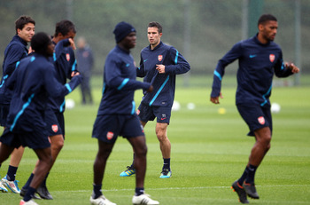 ST ALBANS, ENGLAND - AUGUST 23:  Robin Van Persie overlooks Samir Nasri of Arsenal as they warm up during a training session ahead of their UEFA Champions League Qualifying second leg match against Udinese at London Colney on August 23, 2011 in St Albans,