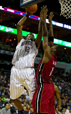 CHARLOTTE, NC - JANUARY 03: Tyrus Thomas #12 of the Charlotte Bobcats shoots over Chris Bosh of the Miami Heat at Time Warner Cable Arena on January 3, 2011 in Charlotte, North Carolina.  The Heat defeated the Bobcats 96-82.  (Photo by Brian A. Westerholt