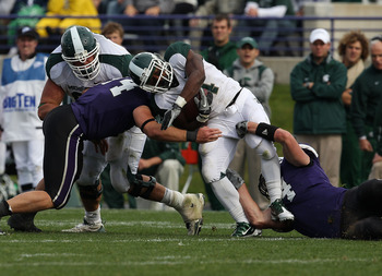 EVANSTON, IL - OCTOBER 23: Edwin Baker #4 of the Michigan State Spartans is tackled by Nate Williams #44 and Vince Browne #94 of the Northwestern Wildcats at Ryan Field on October 23, 2010 in Evanston, Illinois. Michigan State defeated Northwestern 35-27.