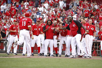 CINCINNATI, OH - AUGUST 28:  Joey Votto #19 of the Cincinnati Reds is greeted by teammates after hitting a game-winning solo home run during the game against the Washington Nationals on August 28, 2011 at Great American Ball Park in Cincinnati, Ohio.  The