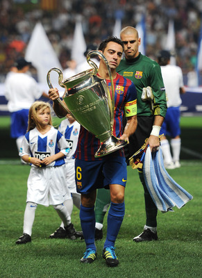 MONACO - AUGUST 26: Captain Xavi Hernandez of FC Barcelona walks with the Champions League trophy prior to the start of the UEFA Super Cup match between FC Barcelona and FC Porto at Louis II Stadium on August 26, 2011 in Monaco, Monaco.  (Photo by Jasper
