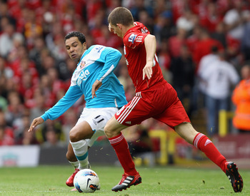 LIVERPOOL, ENGLAND - AUGUST 13:  Kieran Richardson of Sunderland attempts to tackle John Flanagan of Liverpool during the Barclays Premier League match between Liverpool and Sunderland at Anfield on August 13, 2011 in Liverpool, England.  (Photo by Clive
