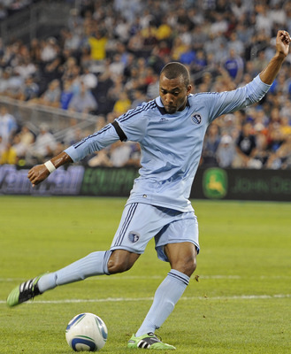 KANSAS CITY, KS - AUGUST 06:  Forward Teal Bunbury (L) of the Sporting Kansas City takes a shot against pressure from defender Jeff Parke (R) of the Seattle Sounders FC during the second half on August 6, 2011 at LiveStrong Sporting Park in Kansas City, K