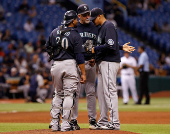 ST. PETERSBURG, FL - AUGUST 19:  Pitching coach Carl Willis #48 (center) of the Seattle Mariners talks with pitcher Felix Hernandez #34 as catcher Miguel Olivo #30 looks on against the Tampa Bay Rays during the game at Tropicana Field on August 19, 2011 i