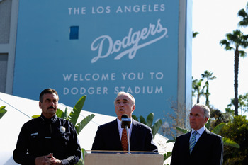 LOS ANGELES, CA - APRIL 14:  Former LAPD chief William Bratton (C) speaks during a news conference at Los Angeles Dodger Stadium as Los Angeles Police Department Chief Charlie Beck (L) and Los Angeles Dodgers owner Frank McCourt listen prior to a game bet