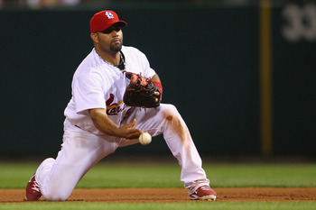 ST. LOUIS, MO - AUGUST 25: Albert Pujols #5 of the St. Louis Cardinals flips the ball to first base at Busch Stadium on August 25, 2011 in St. Louis, Missouri.  The Cardinals beat the Pirates 8-4.  (Photo by Dilip Vishwanat/Getty Images)