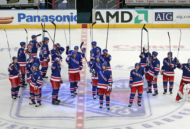 NEW YORK - MARCH 20:  The New York Rangers stand at center ice and raise their sticks in the air to say thank you to the fans (as most of the teams in Europe do after games) after the victory over the Boston Bruins on March 20, 2006 at Madison Square Gard