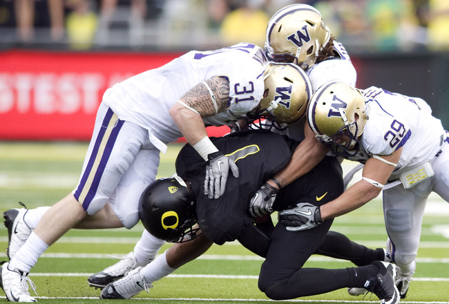 EUGENE, OR - NOVEMBER 6: Quarterback Darron Thomas #1 of the Oregon Ducks is tackled by linebacker Cort Dennison #31 and safety Nate Fellner #29 of the Washington Huskies in the third quarter of the game at Autzen Stadium on November 6, 2010 in Eugene, Or