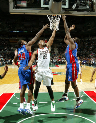 MILWAUKEE - FEBRUARY 20:  Michael Redd #22 of the Milwaukee Bucks puts up a shot between Antonio McDyess #24 (L) and Nazr Mohammed #13 of the Detroit Pistons on February 20, 2007 at the Bradley Center in Milwaukee, Wisconsin. The Pistons defeated the Buck