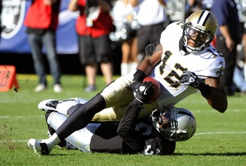OAKLAND, CA - AUGUST 28:  Marques Colston #12 of the New Orleans Saints is dragged down at the one yard line by Tyvon Branch #33 of the Oakland Raiders in the first quarter during an NFL pre-season football game at the O.co Coliseum August 28, 2011 in Oak