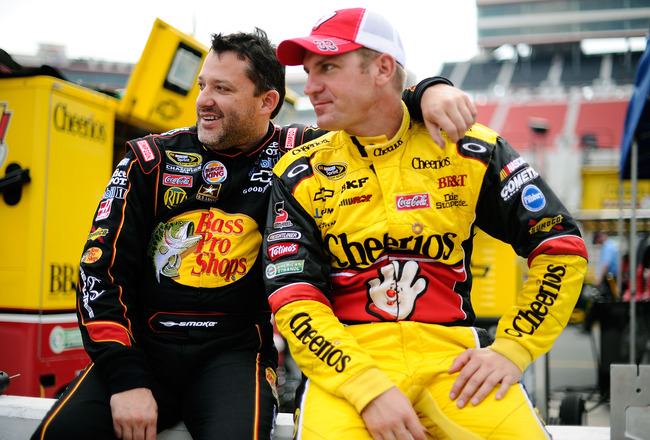 BRISTOL, TN - AUGUST 26:  Tony Stewart(L), driver of the #14 Bass Pro Shops/Office Depot Chevrolet, and Clint Bowyer, driver of the #33 Hamburger Helper Chevrolet, look on from the garage area during practice for the NASCAR Sprint Cup Series IRWIN Tools N