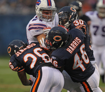 CHICAGO, IL - AUGUST 13: (L-R) Tim Jennings #26, Chris Harris #46 and D.J. Moore #30 of the Chicago Bears bring down Scott Chandler #84 of the Buffalo Bills during a preseason game at Soldier Field on August 13, 2011 in Chicago, Illinois. (Photo by Jonath