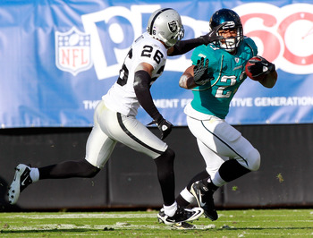 JACKSONVILLE, FL - DECEMBER 12:   Stanford Routt #26 of the Oakland Raiders attempts to tackle Rashad Jennings #23 of the Jacksonville Jaguars during the game at EverBank Field on December 12, 2010 in Jacksonville, Florida.  (Photo by Sam Greenwood/Getty