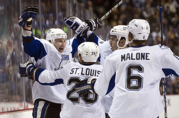 VANCOUVER, CANADA - DECEMBER 11: Steven Stamkos #91 of the Tampa Bay Lightning celebrates with Martin St Louis #26, Ryan Malone #6 and Teddy Purcell #16 after scoring against the Vancouver Canucks in overtime to win 5-4 during NHL action on December 11, 2