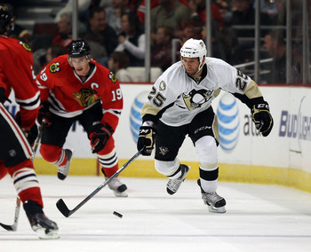 CHICAGO - OCTOBER 01: Max Talbot #25 of the Pittsburgh Penguins skates past Jonathan Toews #19 of the Chicago Blackhawks during a pre-season game at the United Center on October 1, 2010 in Chicago, Illinois. The Blackhawks defeated the Penguins 5-2.  (Pho