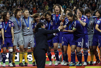 FRANKFURT AM MAIN, GERMANY - JULY 17:  LOC President Steffi Jones (C) hands over the trophy to Homara Sawa of Japan after the FIFA Women's World Cup Final match between Japan and USA at the FIFA World Cup stadium Frankfurt on July 17, 2011 in Frankfurt am