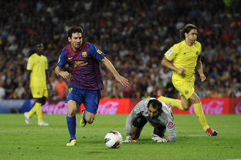BARCELONA, SPAIN - AUGUST 29:  Lionel Messi of FC Barcelona scores his fourth team's goal under a challenge by the goalkeeper Diego Lopez of Villarreal CF during the La Liga match between FC Barcelona and Villarreal CF at Camp Nou on August 29, 2011 in Ba
