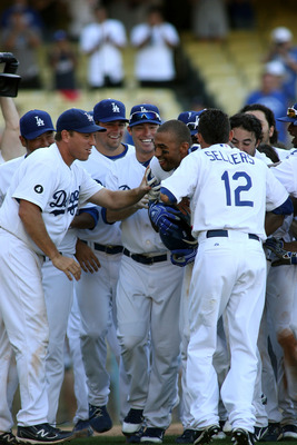 LOS ANGELES, CA - AUGUST 27:  Matt Kemp #27 of the Los Angeles Dodgers is mobbed by teammates at home plate as they celebrate his game-winning solo home run against the Colorado Rockies in the bottom of the 11th inning at Dodger Stadium on August 27, 2011