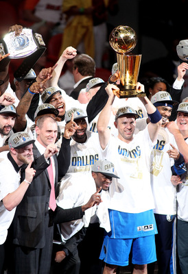 MIAMI, FL - JUNE 12:  Jason Kidd #2 of the Dallas Mavericks holds up the Larry O'Brien Championship trophy as he celebrates with his teammates, head coach Rick Carlisle and team owner Mark Cuban after they won 105-95 against the Miami Heat in Game Six of
