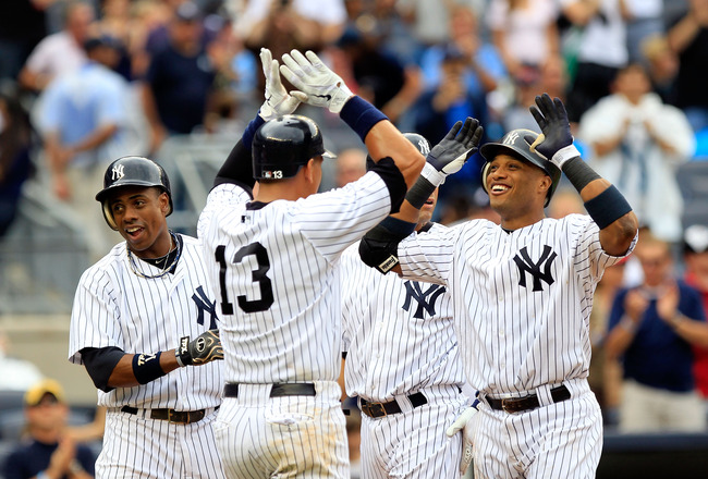NEW YORK, NY - AUGUST 25:  Robinson Cano #24 of the New York Yankees is congratulated by his teammates Curtis Granderson, Alex Rodriguez #13 and Derek Jeter for his grand slam home run in the 5th inning against the Oakland Athletics on August 25, 2011 at