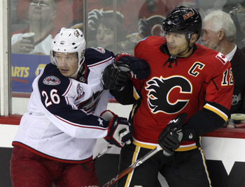 CALGARY, AB - MARCH 4:  Jarome Iginla #12 of the Calgary Flames pushes with Samuel Pahlsson #26 of the Columbus Blue Jackets in the second period of NHL action on March 4, 2011 at the Scotiabank Saddledome in Calgary, Alberta, Canada. (Photo by Mike Ridew