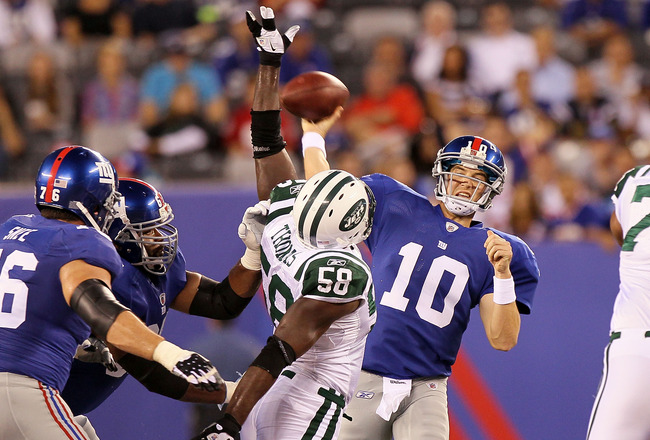EAST RUTHERFORD, NJ - AUGUST 29:  Eli Manning #10 of the New York Giants throws a first half pass under pressure from Bryan Thomas #58 of the New York Jets during their pre season game on August 29, 2011 at MetLife Stadium in East Rutherford, New Jersey.