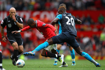MANCHESTER, ENGLAND - AUGUST 28:  Johan Djourou of Arsenal tackles Ashley Young of Manchester United during the Barclays Premier League match between Manchester United and Arsenal at Old Trafford on August 28, 2011 in Manchester, England.  (Photo by Alex
