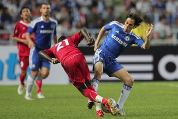 BANGKOK, THAILAND - JULY 24:  Yossi Benayoun #10 of Chelsea contests the ball with Dagno Siaka of Thailand during the pre-season friendly match between the Thailand All Stars and Chelsea at Rajamangala National Stadium on July 24, 2011 in Bangkok, Thailan