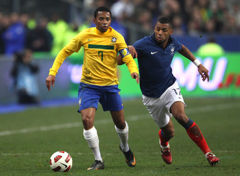 PARIS, FRANCE - FEBRUARY 09:  Robinho of Brazil holds off a challenge from Yann M'Vila of France during the International friendly match between France and Brazil at Stade de France on February 9, 2011 in Paris, France.  (Photo by Alex Livesey/Getty Image