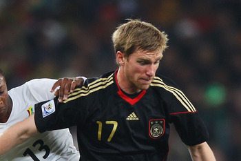 JOHANNESBURG, SOUTH AFRICA - JUNE 23:  Andre Ayew of Ghana challenges Per Mertesacker of Germany during the 2010 FIFA World Cup South Africa Group D match between Ghana and Germany at Soccer City Stadium on June 23, 2010 in Johannesburg, South Africa.  (P