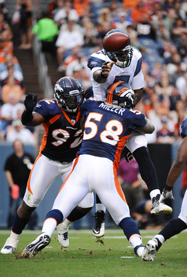 DENVER, CO - AUGUST 27:  Von Miller #58 and Elvis Dumervil #92 of the Denver Broncos hit Tavaris Jackson #7 of the Seattle Seahawks as he throws a pass during the preseason game at Sports Authority Field at Mile High on August 27, 2011 in Denver, Colorado