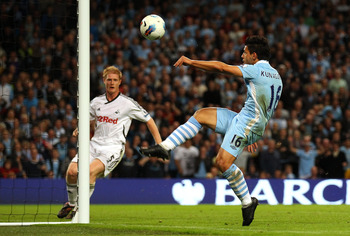 MANCHESTER, ENGLAND - AUGUST 15:  Sergio Aguero of Manchester City chips the ball over to David Silva to score the third goal during the Barclays Premier League match between Manchester City and Swansea City at Etihad Stadium on August 15, 2011 in Manches