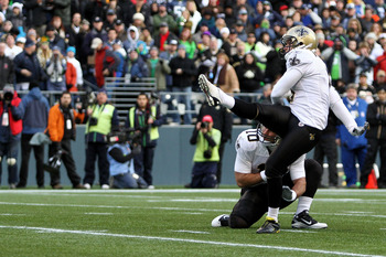 SEATTLE, WA - JANUARY 08:  Garrett Hartley #5 kicks as Chase Daniel #10 of the New Orleans Saints holds against the Seattle Seahawks during the 2011 NFC wild-card playoff game at Qwest Field on January 8, 2011 in Seattle, Washington.  (Photo by Otto Greul