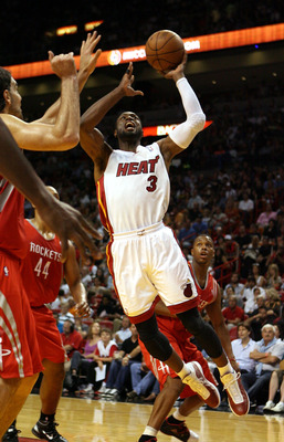 MIAMI, FL - MARCH 27:  Guard Dwyane Wade of the Miami Heat shoots against the Houston Rockets at American Airlines Arena on March 27, 2011 in Miami, Florida. NOTE TO USER: User expressly acknowledges and agrees that, by downloading and/or using this Photo