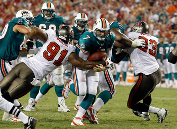 TAMPA, FL - AUGUST 27:  Quarterback Chad Henne #7 of the Miami Dolphins is tackled by defender Da'Quan Bowers #91 of the Tampa Bay Buccaneers during a preseason game at Raymond James Stadium on August 27, 2011 in Tampa, Florida.  (Photo by J. Meric/Getty
